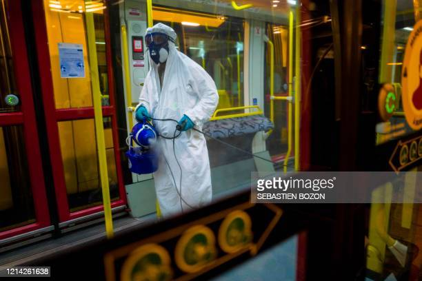 Worker wearing a protective suit and mask, disinfects a tramway at the Solea transport depot in Mulhouse, eastern France, on May 20 as France eases...