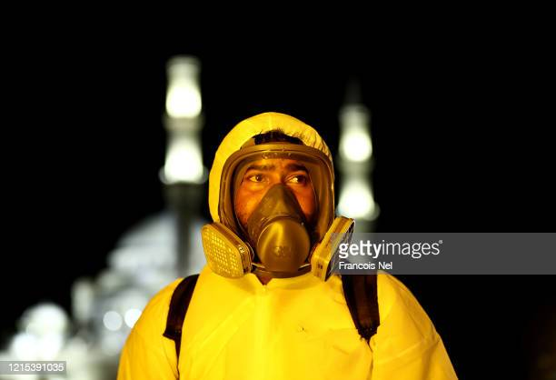 A worker wearing a protective suit and mask sprays disinfectant to stop the spread of the coronavirus on March 28 2020 in Sharjah United Arab...