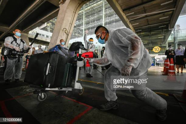 Worker wearing a protective suit disinfects luggage bags as a preventive measure against the spread of Coronavirus at the Suvarnabhumi airport in...