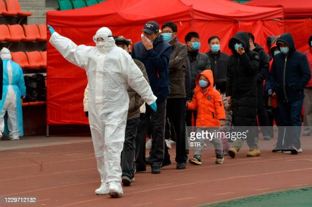 Worker wearing a protective suit leads residents to a makeshift Covid-19 coronavirus testing center in Tianjin on November 21 after new coronavirus...