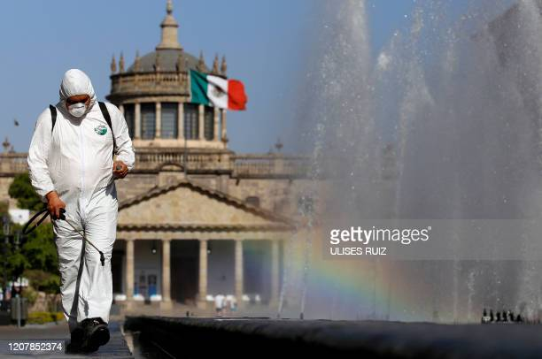 Worker wearing a protective suit sprays disinfectant during a campaign to sanitize public spaces as a preventive measure against the spread of the...