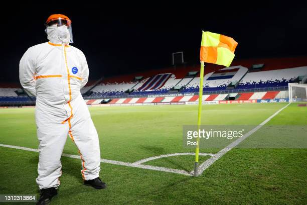 Worker wearing a protective suit stands by the pitch before a third round first leg match between Independiente del Valle and Gremio as part of Copa...