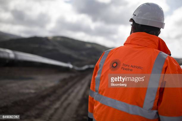 A worker wearing a reflective safety jacket looks towards welded pipes at the 63km point during the construction of the Trans Adriatic gas pipeline...