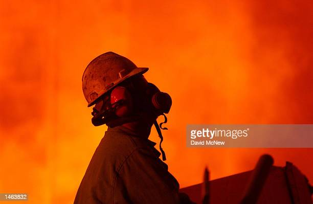A worker wearing a respirator keeps an eye on molten steel at the TAMCO steel mini mill on October 4 2002 in Rancho Cucamonga California TAMCO...