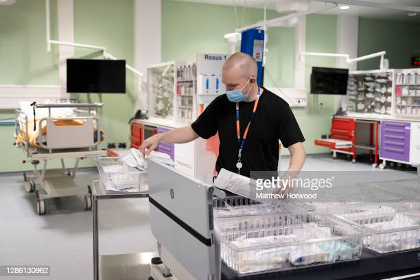 Worker wearing a surgical face mask sorts medical supplies in the accident and emergency department of the new Llanfrechfa Grange Hospital on...