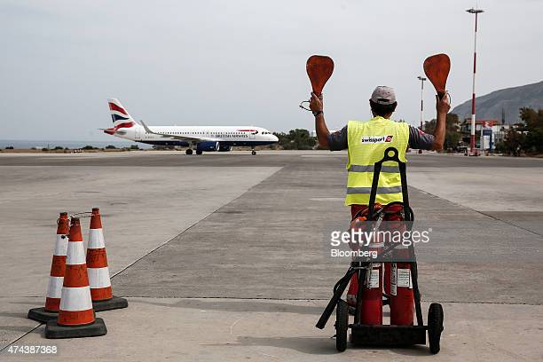 A worker wearing a Swissport International Ltd safety vest signals to a taxiing passenger jet operated by British Airways a unit of IAG SA as it...