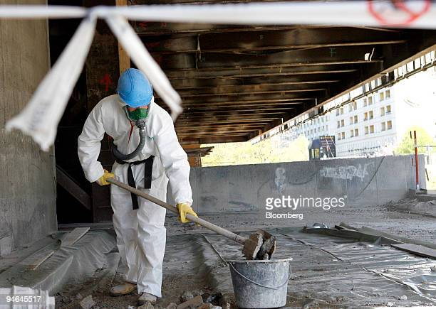 A worker wearing an asbestos suit and a gas mask removes hazardous material while working on the largescale dismantling project to disassemble the...
