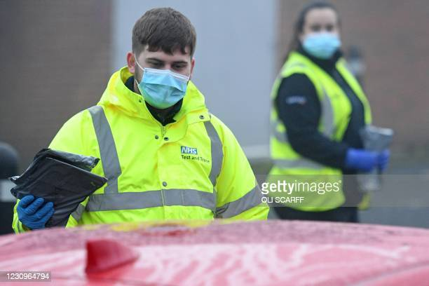 Worker wearing an NHS Test and Trace-branded jacket passes coronavirus test kits to members of the public arriving at a temporary COVID-19 testing...