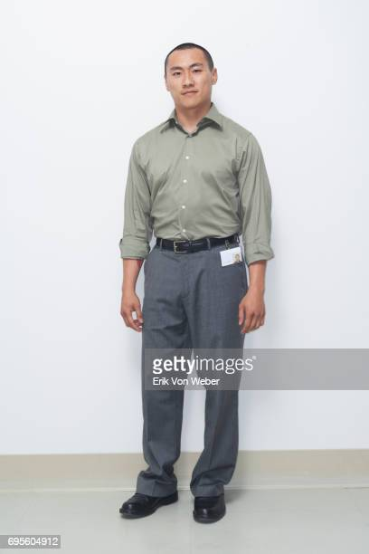 worker wearing button up shirt and slacks standing in front of white wall