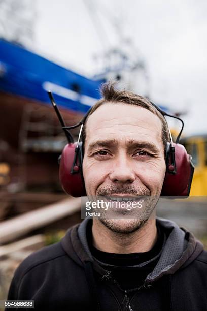 Worker wearing ear protectors at harbor