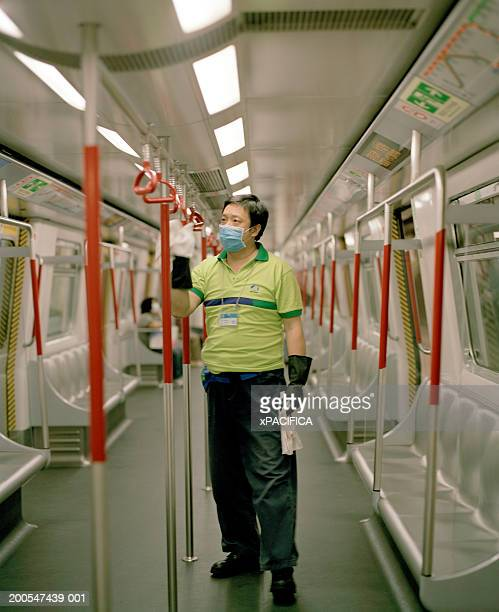 Worker wearing face mask, cleaning handles on train