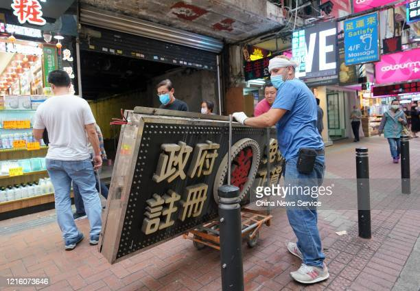 A worker wearing face mask removes the signboard of a closed drug store at Causeway Bay on March 31 2020 in Hong Kong China