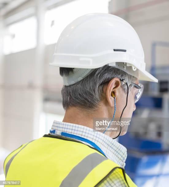 Worker wearing hard hat and ear plugs