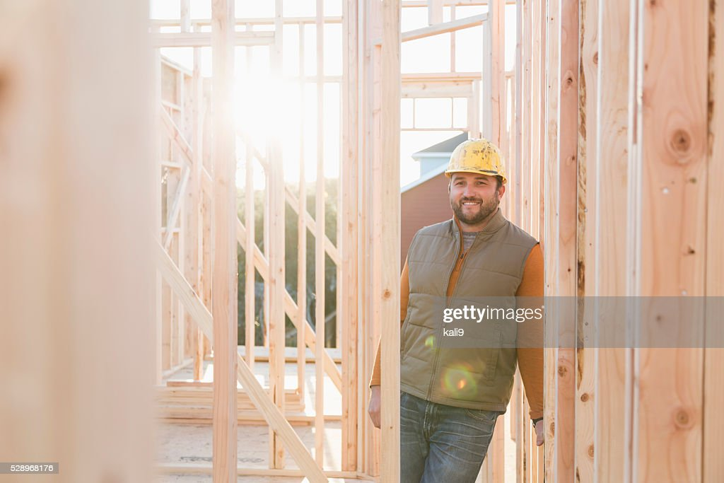 Worker wearing hardhat at construction site : Stock Photo
