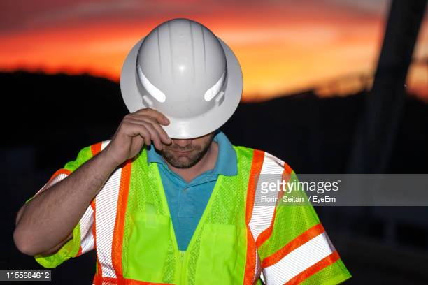 worker wearing hardhat standing against sky during sunset - florin seitan stock pictures, royalty-free photos & images