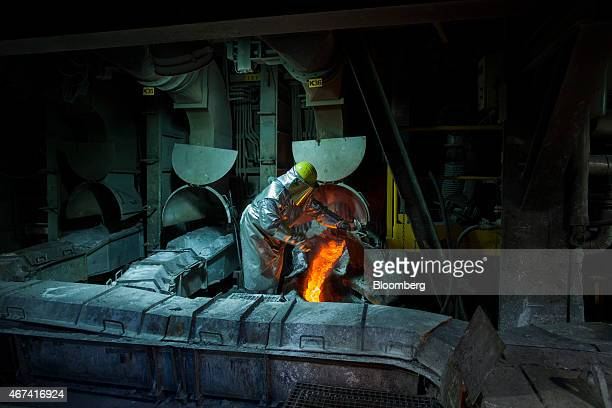 A worker wearing heat resistant clothing checks the flow of molten copper from a hot furnace at the KHGM Polska Miedz SA copper smelting plant in...