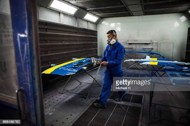 Worker wearing mask spray painting van body in car factory