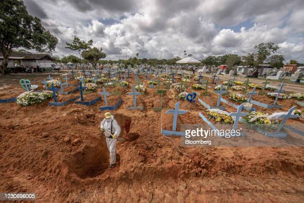 Worker wearing personal protective equipment digs a grave at a cemetery in Manaus, Brazil, on Tuesday, Jan. 19, 2021. Severe oxygen shortages at...