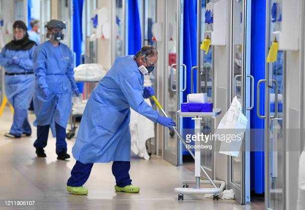 A worker wearing personal protective equipment mops a corridor in the Intensive Care unit at the Royal Papworth Hospital operated by the Royal...