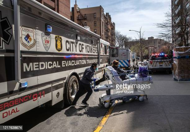 Worker wearing personal protective equipment , pushes a COVID-19 patient from a specialized bus known as a Medical Evacuation Transport Unit , which...