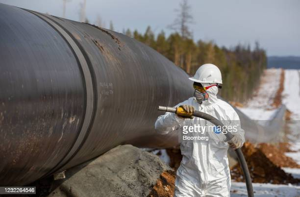 Worker wearing personal protective equipment uses a sandblasting machine to treat the seams of joined pipework during pipeline laying operations for...