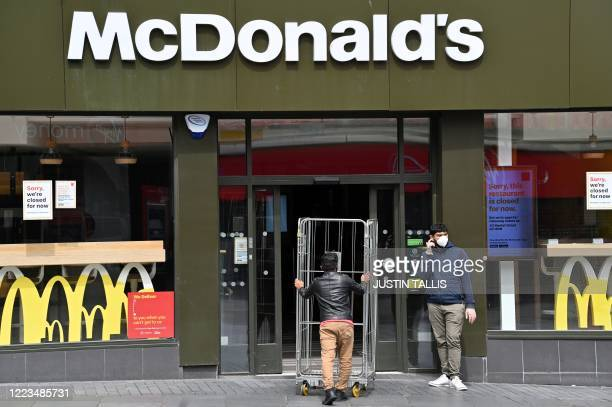 Worker wearing PPE , of a face mask or covering as a precautionary measure against spreading COVID-19, wheels barriers into a branch of McDonalds in...
