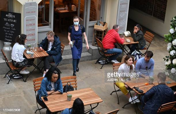 A worker wearing PPE of a face mask or covering as a precautionary measure against spreading COVID19 passes customers sitting at socially distanced...