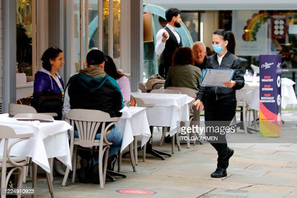 A worker wearing PPE of a face mask or covering as a precautionary measure against spreading COVID19 takes menus to customers sat outside a recently...