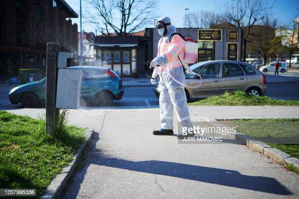 Worker wearing protective clothes disinfects streets in city centre of Kranj, Slovenia on March 23, 2020 amid concerns over the spread of the...