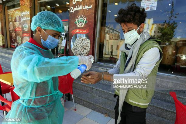 Worker wearing protective clothing sprays hand sanitiser on a customer's hand before he enters a restaurant in the Yemeni capital Sanaa on March 24,...