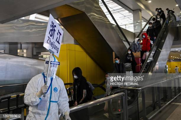 Worker wearing protective gear, amid concerns of the COVID-19 coronavirus, escorts passengers to a bus that will take them to their city in Zhejiang...