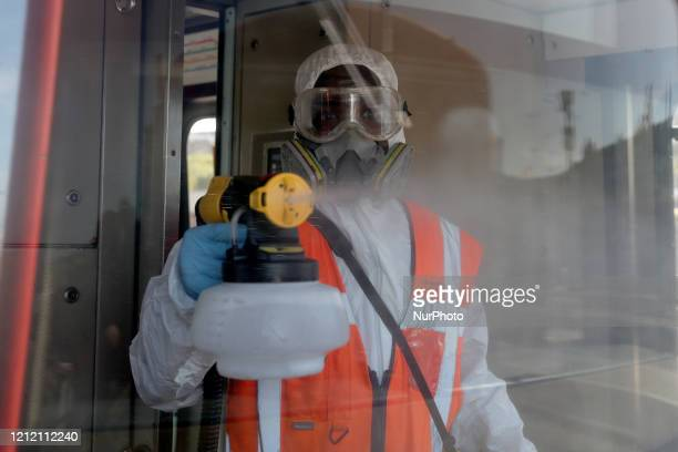A worker wearing protective gear disinfects a metro train at the Metros maintenance workshops in Lisbon Portugal on May 7 amid the COVID19...