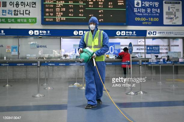 Worker wearing protective gear sprays disinfectant as part of preventive measures against the spread of the COVID-19 coronavirus, at a railway...
