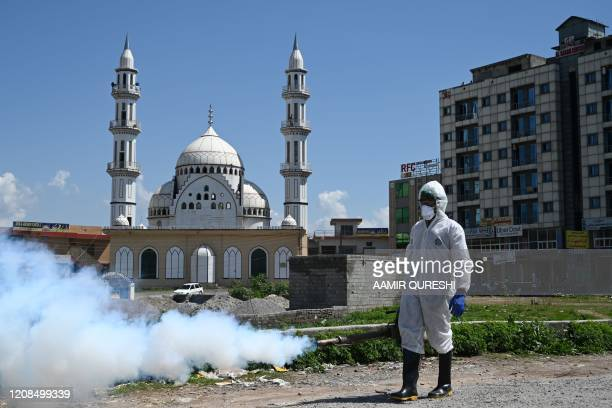 Worker wearing protective gear sprays disinfectant at a street at a residential area during a government-imposed nationwide lockdown as a preventive...