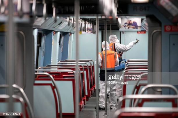 A worker wearing protective gear sprays disinfectant to sanitise a metro train as a preventive measure against the COVID19 coronavirus in Lisbon...