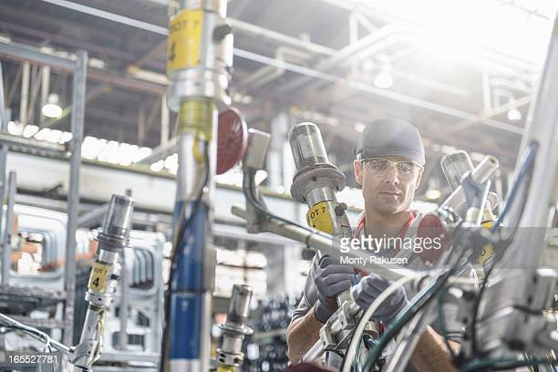 Worker wearing protective goggles inspecting car parts in car plant