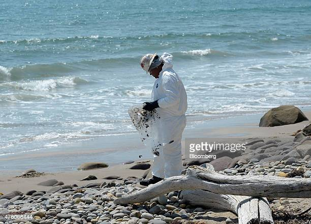 A worker wearing protective overalls removes oil from rocks on Faria Beach in Ventura California US on Friday June 5 2015 A pipeline the oil market...
