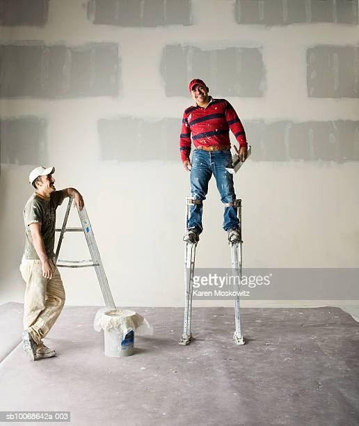 Worker wearing stilts, smiling