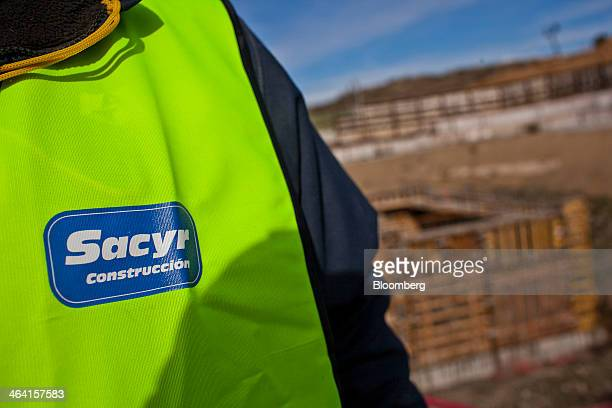 A worker wears a company logo on his vest as he stands at the construction site of an underground rail network a joint project by Sacyr SA and...