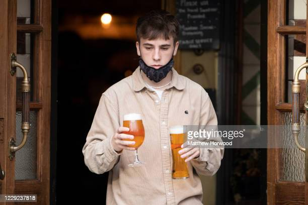 Worker wears a face covering and carries two pints of beer at a bar on St. Mary Street on October 23, 2020 in Cardiff, Wales. Wales will go into a...