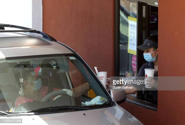 Worker wears a mask and gloves as she hands soft drinks to a customer at a McDonald's drive-thru on April 22, 2020 in Novato, California. McDonald's...