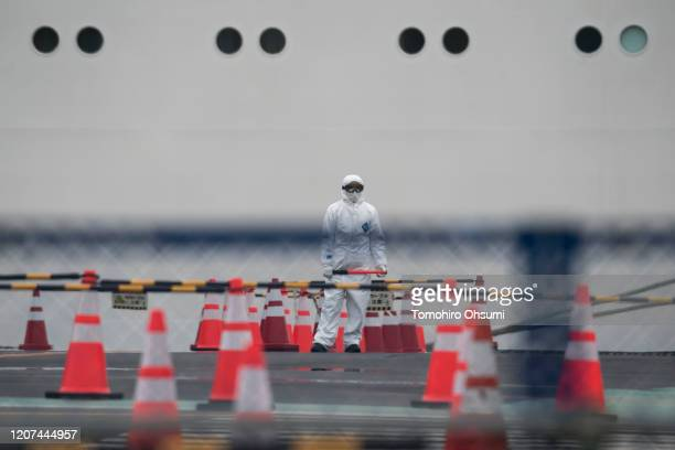 A worker wears a protective suit and a mask as he works in front of the quarantined Diamond Princess cruise ship docked at the Daikoku Pier on...