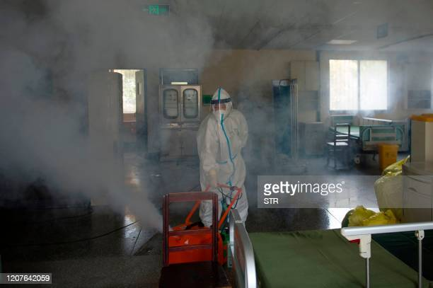 TOPSHOT A worker wears a protective suit as he disinfects a room in the Wuhan No7 hospital in Wuhan in China's central Hubei province on March 19...