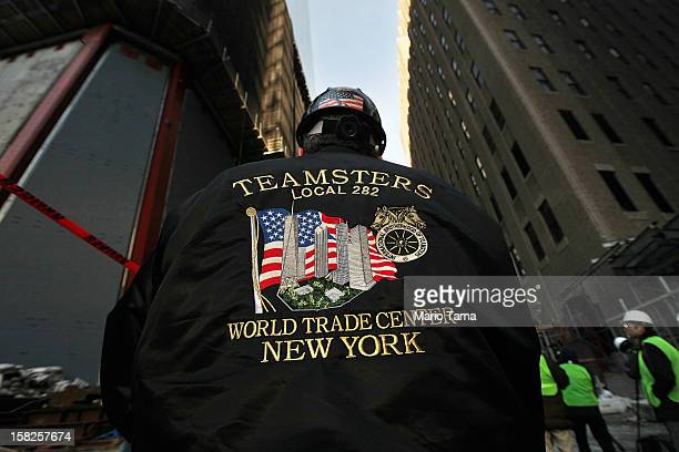 A worker wears a Teamsters union jacket as the first piece of the spire is hoisted atop One World Trade Center on December 12 2012 in New York City...