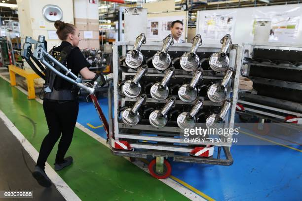 A worker wears an exoskeleton as she pushes a trolley laden with components at a Renault factory in Cléon northwestern France on June 6 2017 / AFP...