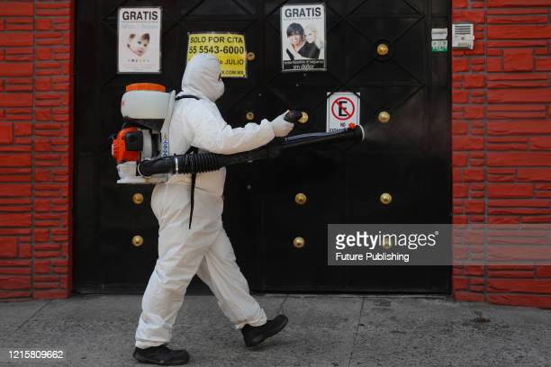 A worker wears protective gear as precautionary measure to sanitize the Naples clinic as attempt to prevent COVID19 spread amid the new virus...