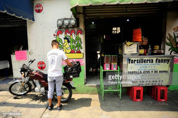 A worker wears protective mask while ready the order for home delivery The Tortilleria Fanny make tortillas of differents flavors as nopal amaranth...
