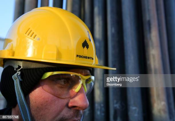 A worker wears safety glasses and a helmet while working with oil pipes on a drilling rig operated by Rosneft PJSC in the Samotlor oilfield near...