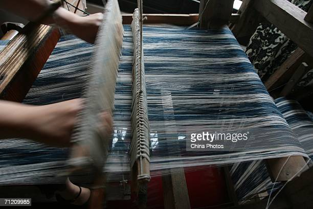 A worker weaves cloth at a Chinese Blue Calico workshop on June 14 2006 in Nantong of Jiangsu Province China Blue Calico is a kind of cloth like...