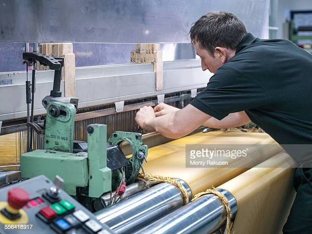 worker weaving kevlar fabric in carbon fibre factory - monty rakusen stock pictures, royalty-free photos & images